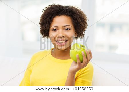 people, food, healthy eating and dental care concept - happy african american young woman with green apple at home