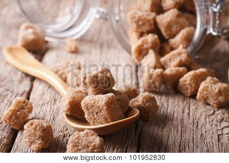 Chipped Brown Cane Sugar Macro In A Wooden Spoon. Horizontal