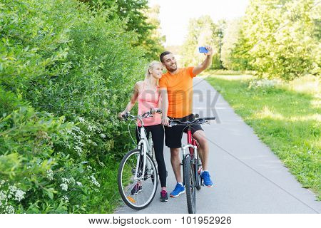 fitness, sport, people, technology and healthy lifestyle concept - happy couple with bicycle taking taking selfie by smartphone outdoors