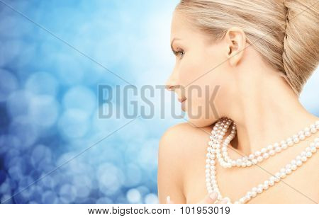 beauty, luxury, people, holidays and jewelry concept - beautiful woman with sea pearl necklace or beads over blue lights background