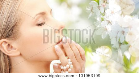 beauty, luxury, people, holidays and jewelry concept - beautiful woman with sea pearls beads in hand over cherry blossom background
