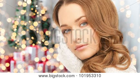 winter holidays, christmas and people concept - happy young woman in mittens touching her face over christmas tree lights background