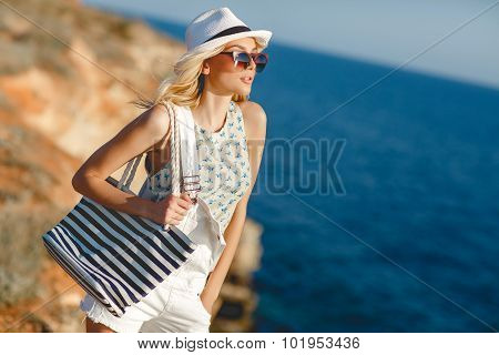 Beautiful woman on a rocky seashore