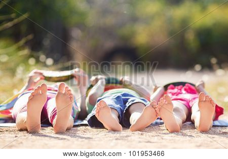 Children lie on the ground in the Park and eat watermelon