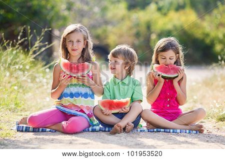 Three happy smiling child eating watermelon in park.