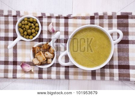 A Delicious Pea Cream With Aromatic Spices On A Wooden Table.