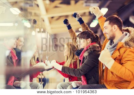 people, friendship, sport and leisure concept - happy friends watching hockey game or figure skating performance on skating rink