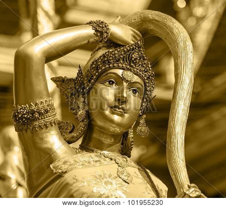 Earth Goddess Bronze Statue  Closeup On Face In Thai Style Temple Golden Color Tone