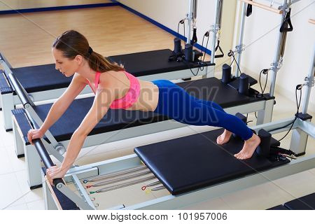 Pilates reformer woman long stretch exercise workout at gym indoor