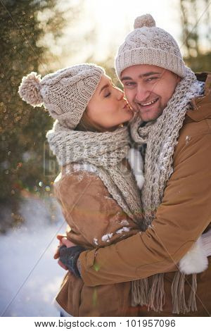 Amorous young woman kissing her happy boyfriend on winter day