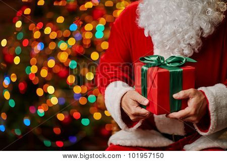 Red giftbox bound by silk green ribbon held by Santa