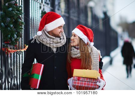 Amorous Santas with giftboxes looking at one another outdoors