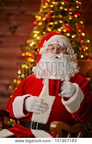 Joyful Santa with cup of latte sitting in armchair in front of camera