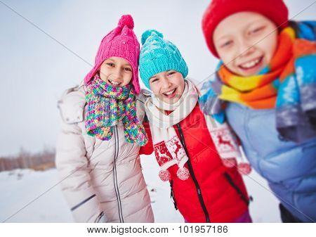 Laughing kids in winterwear having fun outdoors