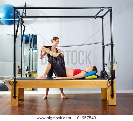 pregnant woman pilates reformer leg spring  exercise workout with personal trainer