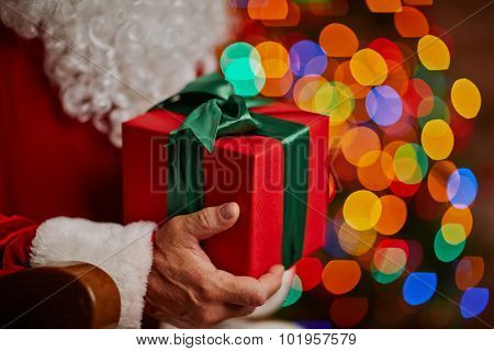 Red box with Christmas gift in Santa hands
