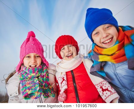 Joyful kids in winterwear looking at camera with smiles