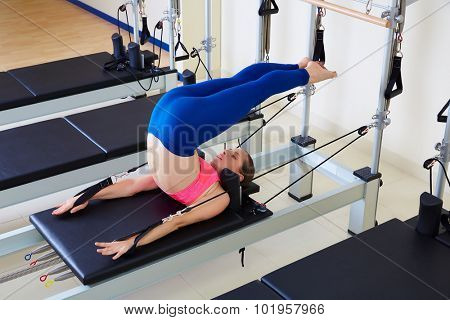 Pilates reformer woman over head exercise workout at gym indoor