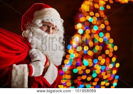 Santa Claus holding big sack with gifts