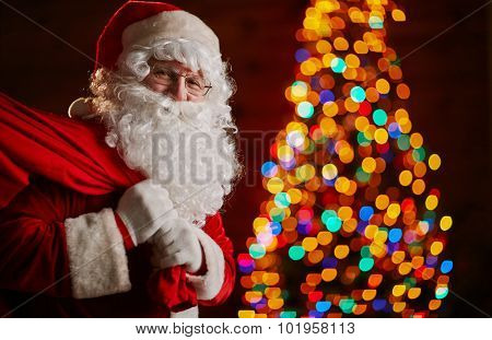 Santa Claus holding carrying sack with gifts for kids
