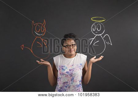 African Woman With An I Don't Know Angel And Devil Gesture On Blackboard Background