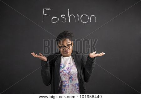 African Woman With An I Don't Know About Fashion Gesture On Blackboard Background