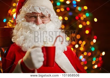 Santa Claus with red cup looking at camera