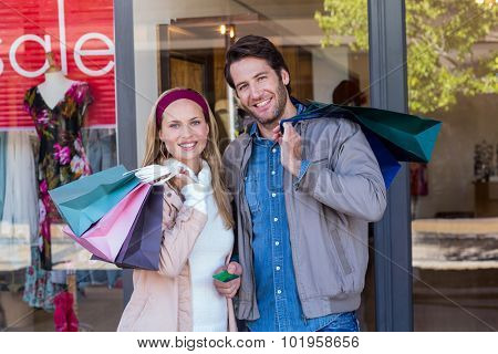 Portrait of smiling couple with shopping bags in front of window at shopping mall