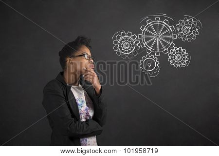 African Woman With Hand On Chin Thinking With Gears On Blackboard Background