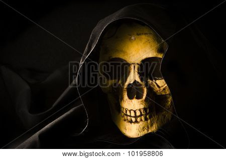 Halloween concept of scary skull head in black hood