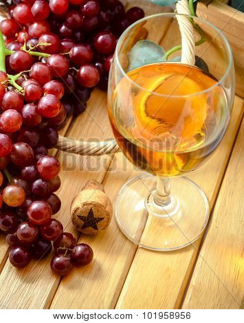 close up shot of wine glass with bunch of grapes