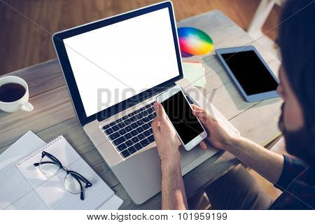 High angle view of editor using smartphone and laptop in creative office
