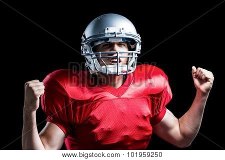 Portrait of American football player cheering with clenched fist standing against black background