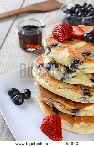 Closeup of a homemade blueberry pancake breakfast with syrup pitcher, wooden spatula, blueberry bowl and strawberries. Vertical format with shallow depth of field.