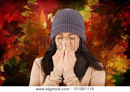 Sick brunette blowing her nose against autumnal leaf pattern in warm tones
