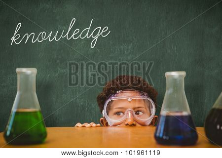 The word knowledge and cute pupil dressed up as scientist against green chalkboard