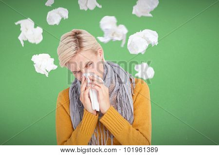 Close up of woman blowing her nose against blue background