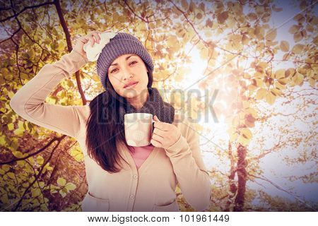 Sick brunette holding a mug and looking at the camera against tranquil autumn scene in forest