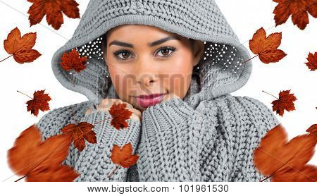 Pretty girl in winter jumper looking at camera against autumn leaves pattern