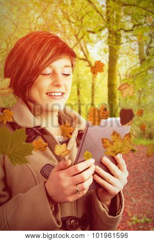 Pretty woman in winter coat using digital tablet against peaceful autumn scene in forest