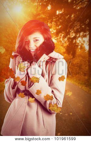 Portrait of beautiful woman in winter coat against autumn scene