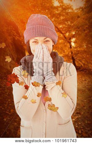 Smiling brunette wearing warm clothes against autumn scene