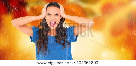 Angry brunette shouting at camera against golden leaves