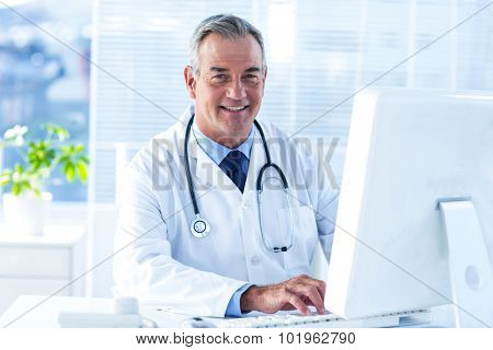 Portrait of male doctor workin on computer in clinic
