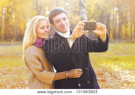 Portrait Of Happy Smiling Young Couple Together Making Selfie On Smarphone In Autumn Park