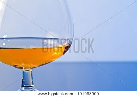 Snifter Of Brandy In Elegant Typical Cognac Glass On Blue Light Background