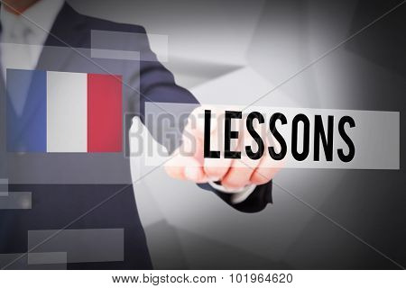 The word lessons and smiling businessman in suit pointing against abstract grey room