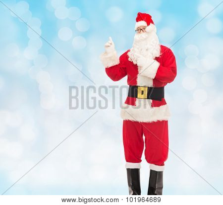 christmas, holidays, gesture and people concept - man in costume of santa claus pointing fingers over blue lights background