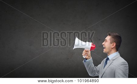 business, people, communication and public announcement concept - happy businessman in suit speaking to megaphone over dark gray concrete wall background