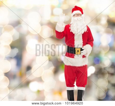 christmas, holidays, gesture and people concept - man in costume of santa claus waving hand over lights background